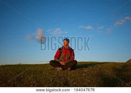 Happy Man Traveler Relaxes On The Alpine Meadow