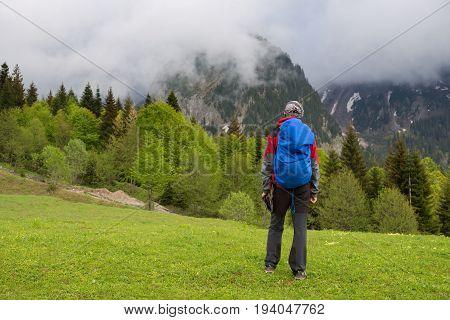 Man Traveler Is Walks Along Alpine Meadow After Storm