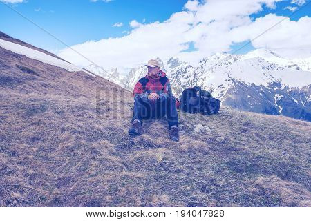 Tired Adventurer Restes, Sitting Next To Backpack On The Mountains