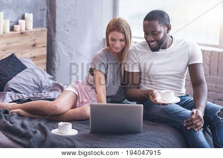 Full of positive emotions. Involved glad international couple sitting in the bedroom and drinking coffee while enjoying weekend and using laptop