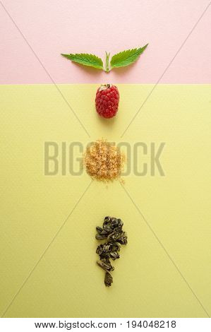 Raspberries, Sugar, A Mint Leaf And A Handful Of Green Tea On A Pastel Yellow-green Background.