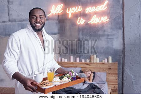 All you need is love. Smiling charming handsome African American man standing in the bedroom and holding the breakfast tray while expressing happiness and waiting for the girlfriend waking