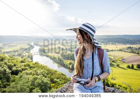 Young woman tourist in hat enjoying sunset view on the beautiful landscape with Dordogne river in France