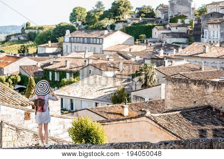 Beautiful sunset view on Saint Emilion village with woman tourist in Bordeaux region in France