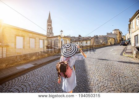 Young woman tourist walking old street at the famous Saint Emilion village in Bordeaux region in France