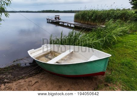 Fisherman's boat and bridge with fishing poles in rainy evening at Masuria lake Inulec Poland