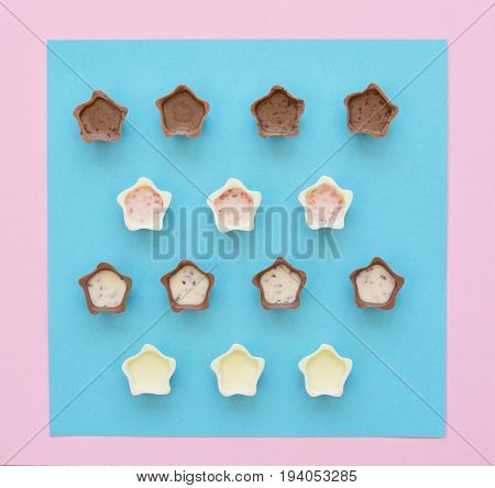Top view of various chocolate pralines on pink and blue background. Flat lay style.