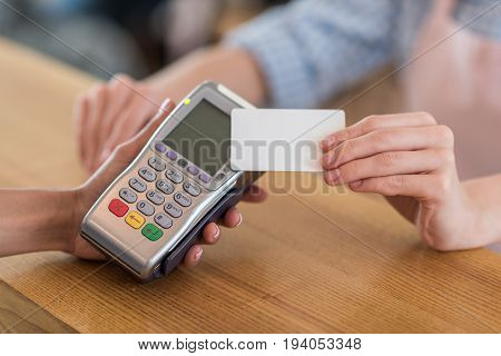cropped shot of woman using credit card for payment in cafe