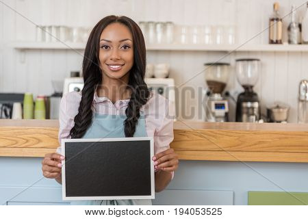 afro-american waitress holding empty board and looking at camera while standing at cafe