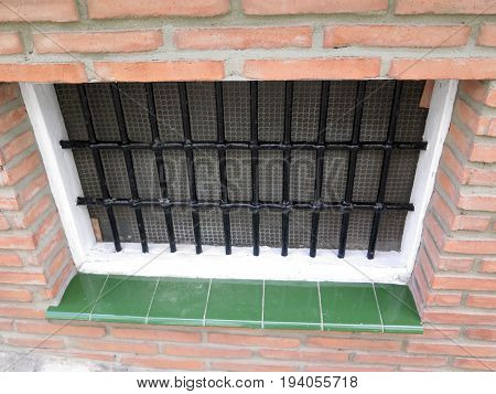 Barred basement window with green glossy tiles