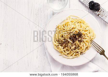Strangozzi italian wheat pasta with truffle on a light background.