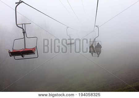 Early in the morning a mountain lift takes tourists to a sleeping mountain enveloped in a very dense fog