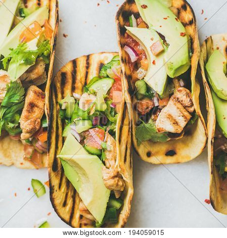 Healthy corn tortillas with grilled chicken fillet, avocado, fresh salsa, limes over light grey marble table background, top view, square crop. Gluten-free, allergy-friendly, weight loss concept