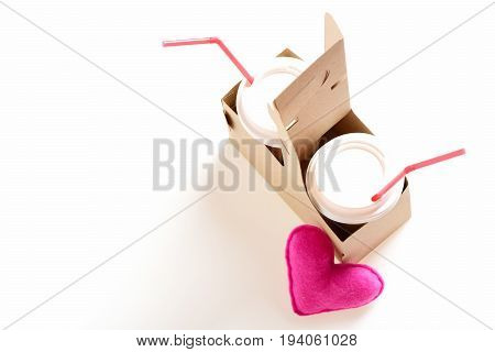 Takeaway composition with plastic disposable cups and straws placed in cardboard package with pink toy heart put near it isolated on white background. Concept of valentines day drinks