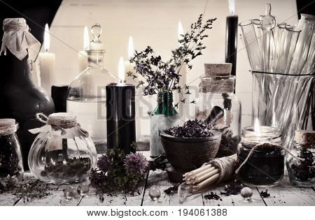 Toned still life with alchemical jar and bottles and mystic objects on the table. Alternative medicine, old pharmaceutic and homeopathic concept. Mystic and occult still life, vintage background