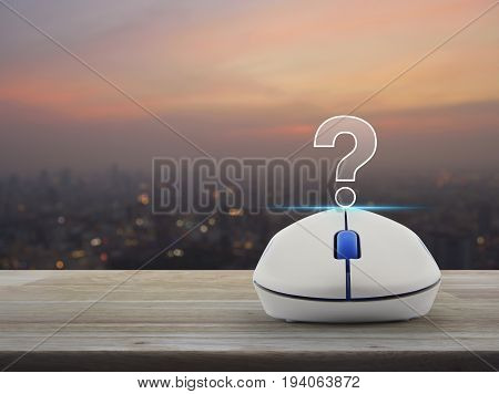 Question mark sign icon with wireless computer mouse on wooden table over blur of cityscape on warm light sundown Customer support concept
