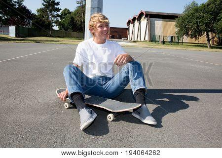 Cute Teenager Blond Boy On Sitting On Skateboard