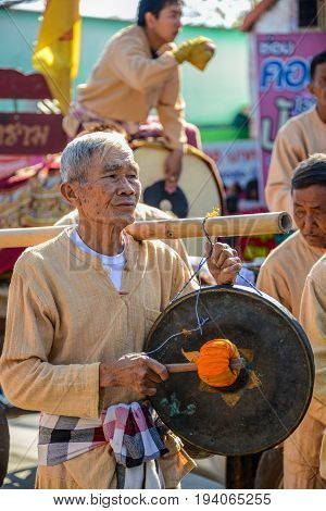 CHIANGMAI THAILAND - JANUARY 25 2015: Indigenous senior holding and hitting gong in parade of 22nd Traditional Skirt Fabric and The Indigenous Product and Culture Festival in Mae Chaem Chiangmai Thailand