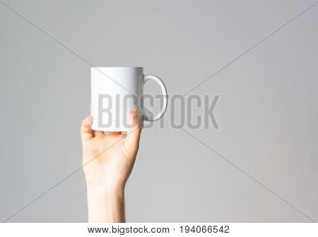 Hand holds coffee mug in hand layout on white background mock up free space