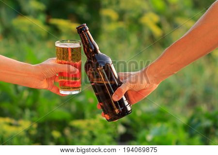 Cropped image of woman and man clanging glass of beer and bottle of beer together on natural green blurred background. Woman clinked her glass against man with bottle