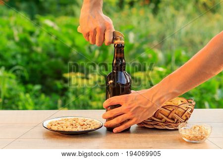 Young man opening bottle of beer with old opener. Brown bottle of beer with potato chips in wicker basket peanuts in plate and bowl on wooden table