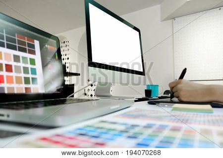 Side view of an artist drawing something on graphic tablet at the office. Blank screen monitor for graphic display montage.