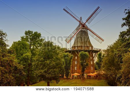 old wind mill among the green trees in the Park toned