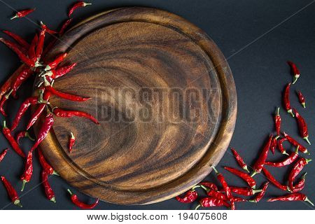 Red chili pepper and wooden board on a black background.