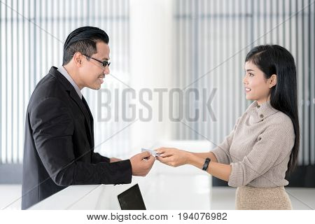 Asian businessman check in at hotel reception front desk.
