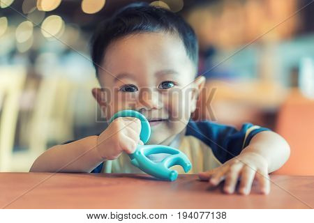 9 months old Asian baby boy sucking his rubber bite toy for relieves toothache.