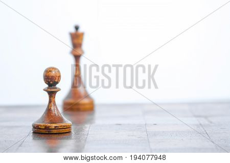 Old chess Board with wooden pieces on a white background.