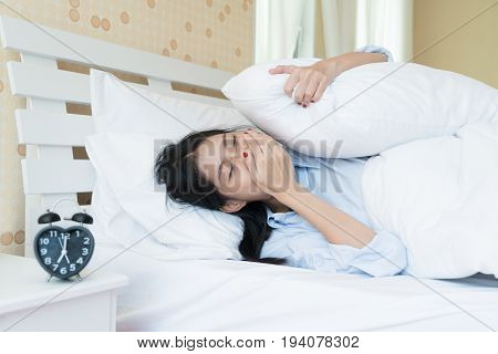 Asian woman yawn and awake up with clock alarm in her bedroom at home. Asian woman lazy wake up to work in morning Monday.