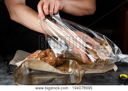 Man packs marinated pieces of meat of pork shoulder in roasting sleeve