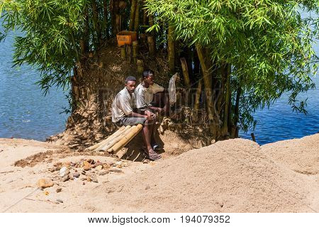 Toamasina Madagascar - December 22 2017: Unidentified Madagascar men - Loaders of sand rest on the river bank near the city of Toamasina (Tamatave) Madagascar East Africa. Everyday life on the river.