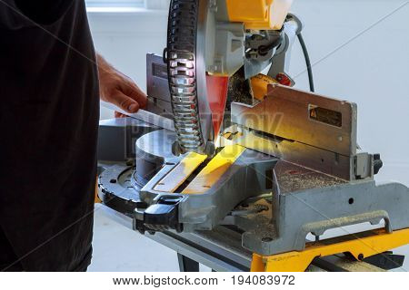 Man Cutting Shoe Moulding On Electric Saw