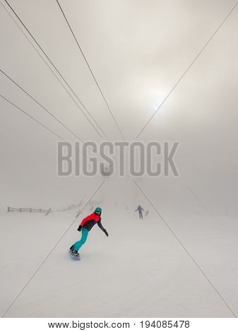 Snowboarder woman in fluorescent overalls and some skiers in thick fog with translucent sun and visible cable car lift.