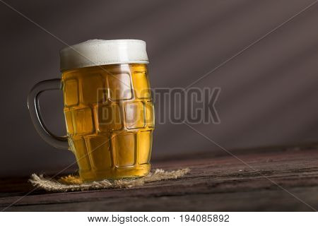 Jug of cold pale beer placed on a burlap cover on a rustic wooden table. Selective focus