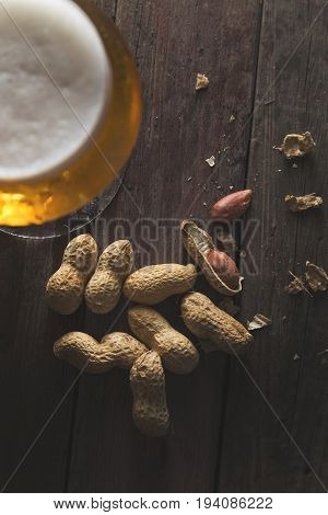 Top view of a glass of cold pale beer with some peanuts on a rustic wooden table. Selective focus on the peanuts