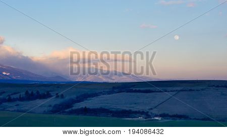 Spring foothills with snowy and cloudy high mountains at twilight.