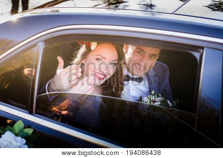 Happy Newlyweds Show Their Hands With Wedding Rings Through Car's Window