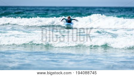 Surfer Woman With Surfboard Is Paddling On The Wave.
