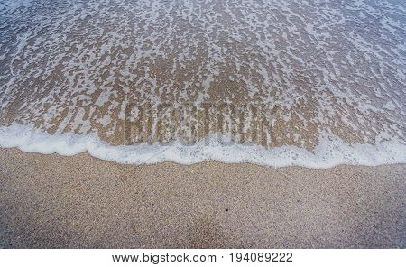 Small ocean sea waves on sandy beach in calm weather. Background landscape picture of dusk or dawn at the Atlantic ocean beach with small waves at low tide.
