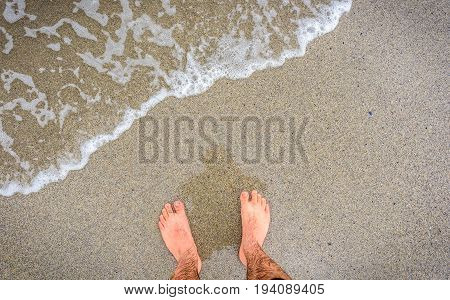 Person Standing In Ocean Sea Waves On Sandy Beach.