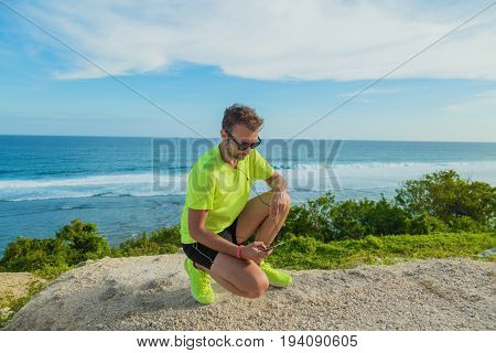 Jogger / runner holding a cellphone with earbuds outdoors.