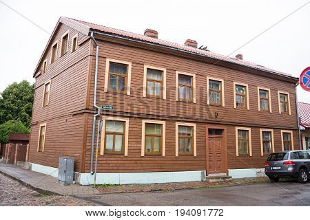 LIEPAJA LATVIA - JULY 25 2016: View of the street with wooden old building in Liepaja Latvia.Typical old residential wooden house