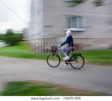 Woman Cyclist In Traffic On The City Roadway