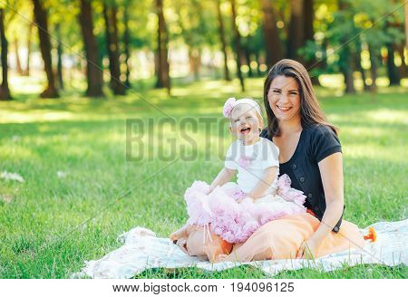 beautiful young mother and daughter sitting on the grass. Beautiful summer background grass meadow trees.