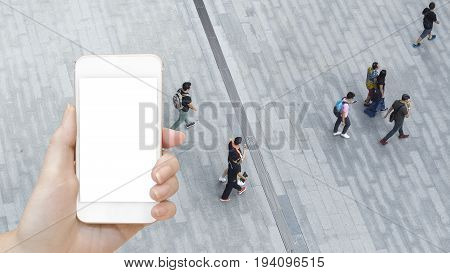 Man's hand shows mobile smartphone with white screen in vertical position with background of people walk on open space concrete pavement from top view bird eye view