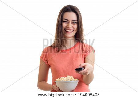 Happy young girl watching a tv with pop-corn isolated on white background