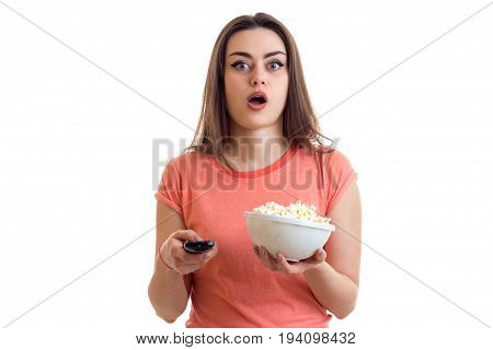 surprised young girl watching a tv with pop-corn isolated on white background